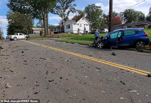 The wrecked vehicles after the crash, with debris from the impact strewn across the street