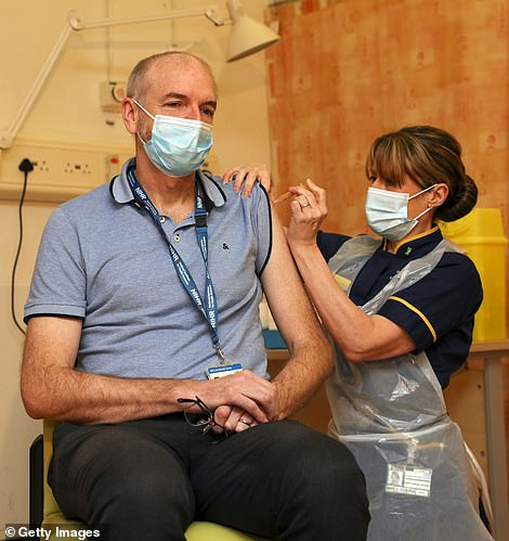 The report concluded that the vaccine programme was 'one of the most stunning scientific achievements in history' and that it 'redeemed' many of the UK's other policy failings. Pictured: Professor Andrew Pollard receives the AZ vaccine in January