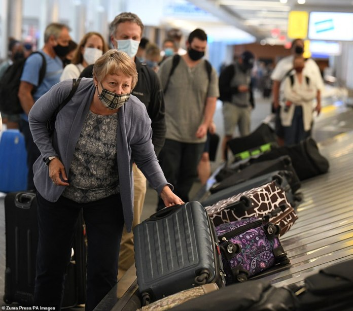 A woman claims her baggage at the arrival terminal at General Mitchell International Airport in Milwaukee on Monday