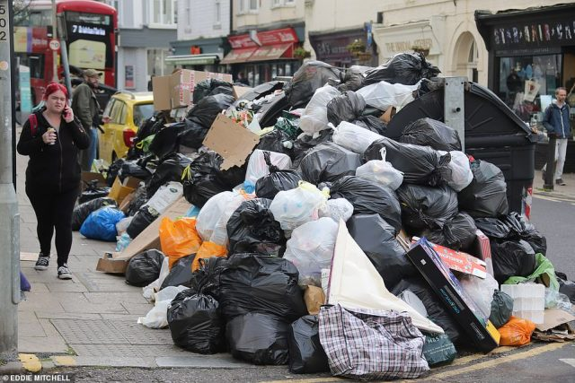 Mountains of rotting rubbish are piling up 10ft high across Brighton because of a row between truck workers on strike and Green councillors which has rumbled on for the past week