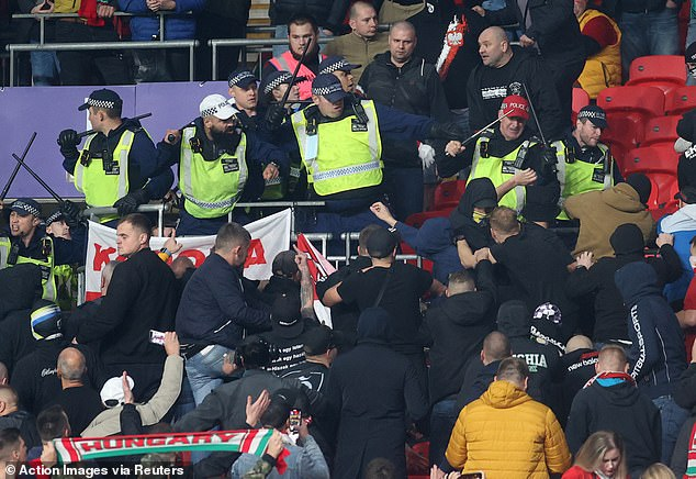 Riot police attempt to push back Hungary fans who were climbing over seats at Wembley