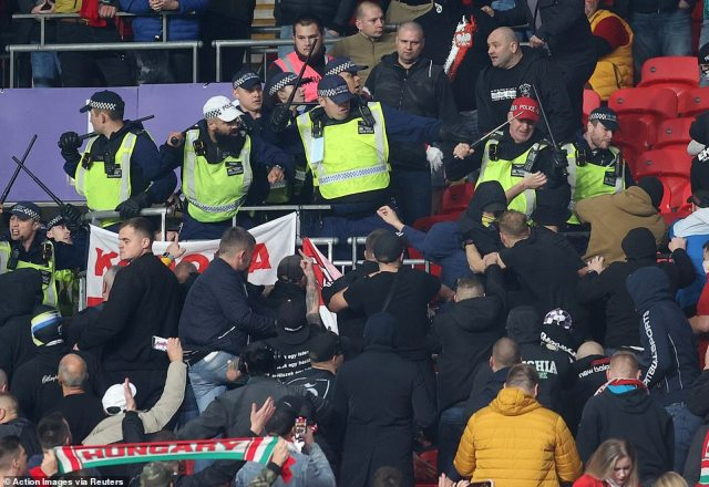Riot police attempt to push back Hungary fans who were climbing over seats at Wembley in shocking scenes on Tuesday
