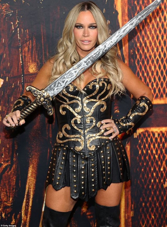 Showbiz legacy: The daughter of John Mellencamp brought a massive toy sword with her to complete the outfit, brandishing it as she mugged for the cameras at the big premiere