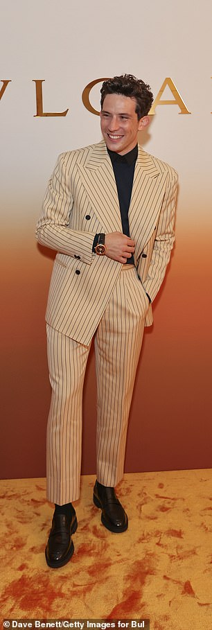 Quirky: Josh looked smart in a cream pinstripe suit over a black shirt