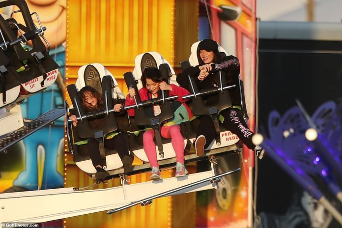 FUN TIME: Megan Fox giggled with joy on a rollercoaster ride as she treated her kids to a day in London on Monday after heading to the UK for The Expendables 4 filming.