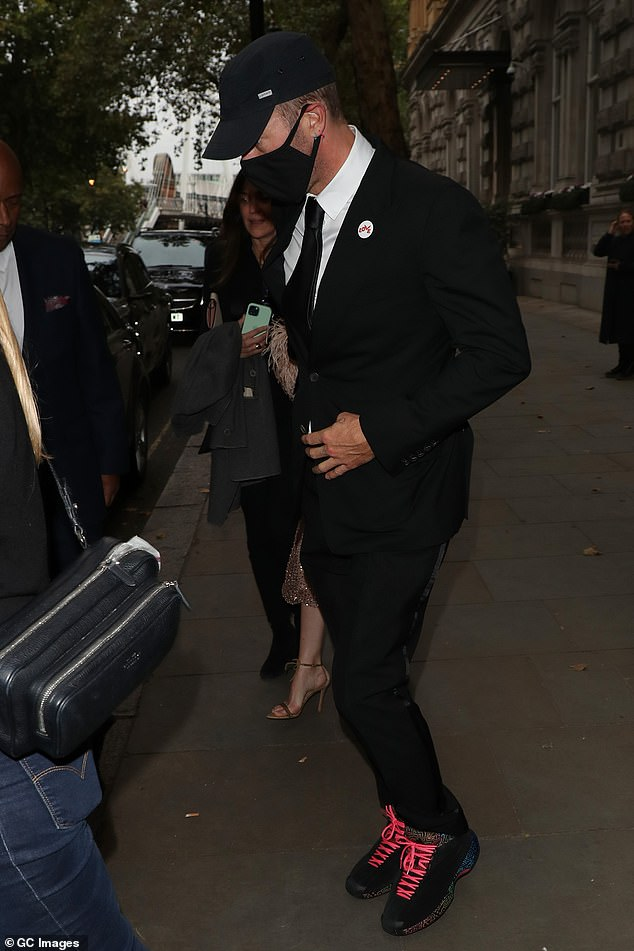 On the move:Chris was snapped leaving The Corinthia Hotel in central London earlier in the night, suited up, with Dakota by his side