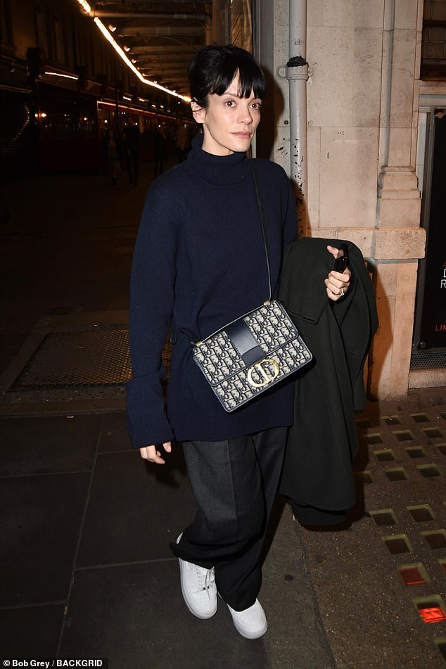 Laid back: The hit-maker, 36, cut a casual figure in a navy oversized jumper as she headed for drinks with friends in London