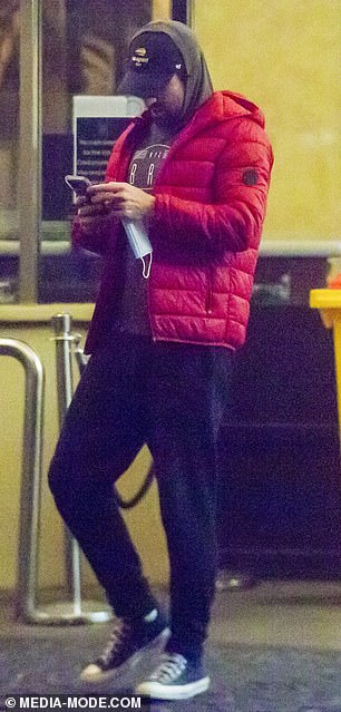 Wrapped up: Kyrgios covered up in a red puffer jacket