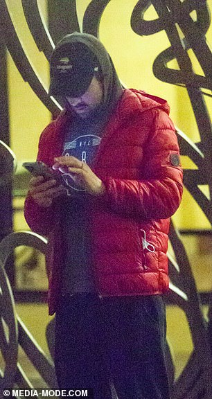 Checking the latest news? The sports star kept himself busy by flicking through his phone