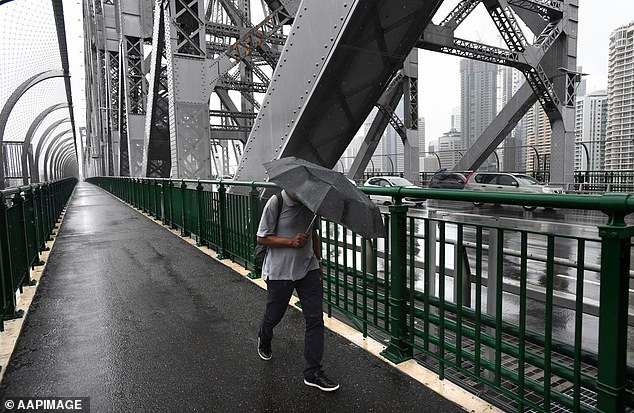 Meteorologists recommend keeping an eye out for weather warnings throughout the week as the wild weather is set to continue (pictured: pedestrians cover up from the rain lashing Brisbane)