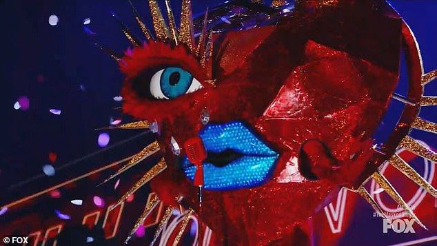 French Language: Queen of Hearts, wearing a giant red heart outfit with blue lips and long golden nails, took the stage and sang 'La Vie En Rose' by Edith Piaf in French