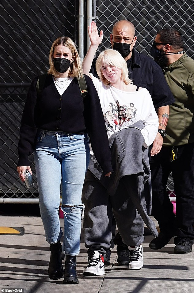 Friendly: After waving to onlookers, she ultimately threw a black hoodie over her shaggy blonde bob, before getting glammed up for her late-night show appearance