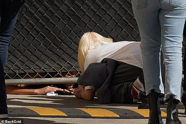 Kind: Billie crouched down on her hands and knees so she could reach under a metal fence and better interact with her die-hard fans