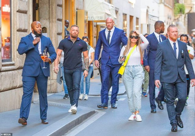 Portrait of a tough guy! Mixed martial arts superstar Conor McGregor was flanked by a huge team of FOUR security guards - one of whom carried his Aperol Spritz for him while on holiday in Rome on Wednesday