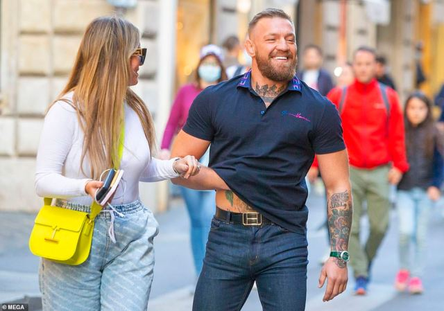 Dressed down: Conor kept it casual in his navy T-shirt and lifted it up slightly to flash his torso tattoos
