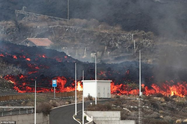 Lava rolls down to a road in Los Llanos, La Palma, on Wednesday, burning shrubbery in its path