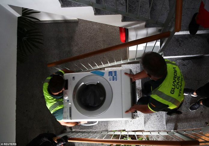 Some residents and tourists have been evacuated to the nearby island of Tenerife to escape the lava flow. Pictured: Civil Guard officers carry a washing machine out of an evacuating resident's home