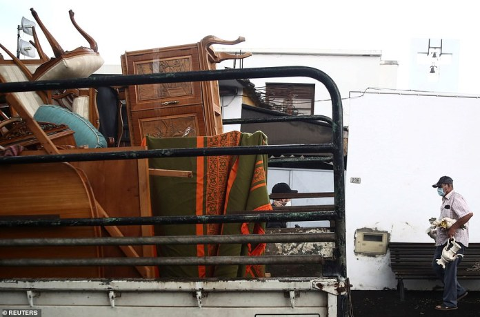 Pictured: Items belonging to Enrique Gonzalez and his family are piled onto the back of a truck as they prepare to leave their home in La Laguna, La Palma on Tuesday