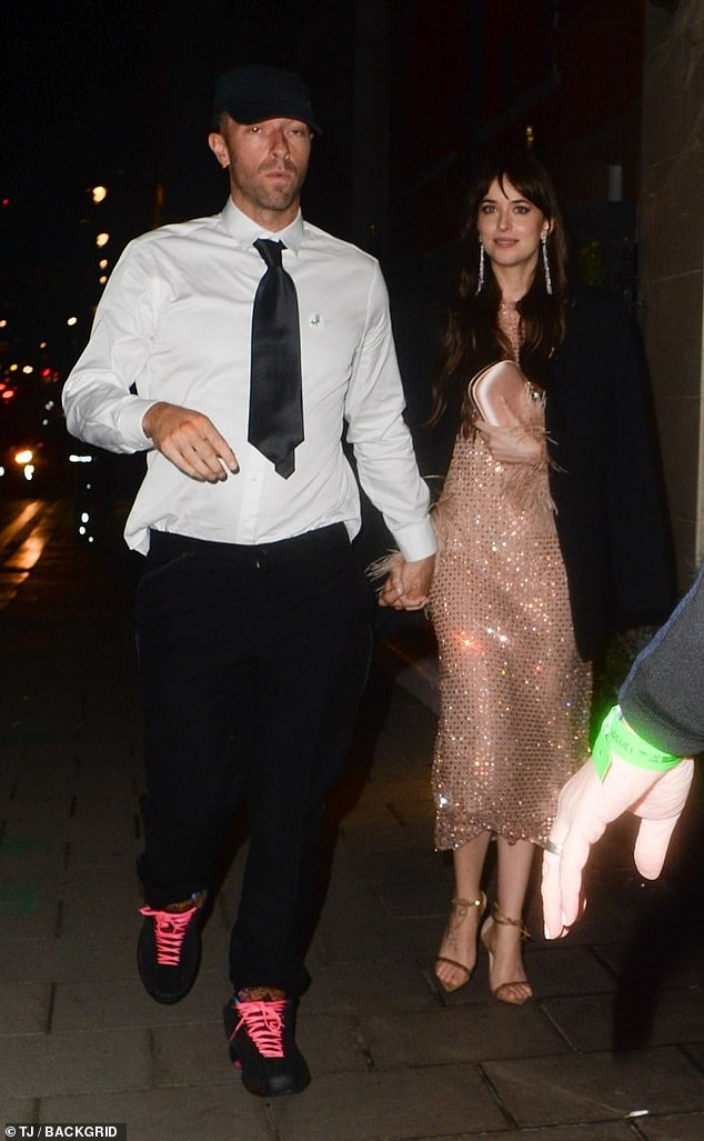Couple: Dakota Johnson put on a loved-up display with her beau Chris Martin as they attended the London premiere of her new film The Lost Daughter on Wednesday