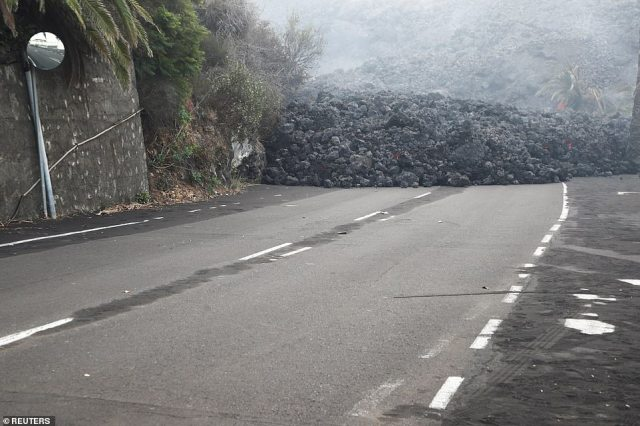 A huge deposit of lava from the Cumbre Vieja volcano has made this road, pictured on Thursday, completely impassable