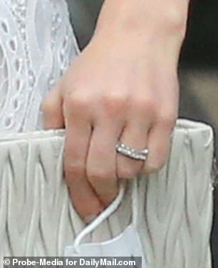 Something old, something new! The ring that Nayel, 30, proposed with features a large center diamond that is flanked by two smaller stones, while her new ring is a chunky diamond band