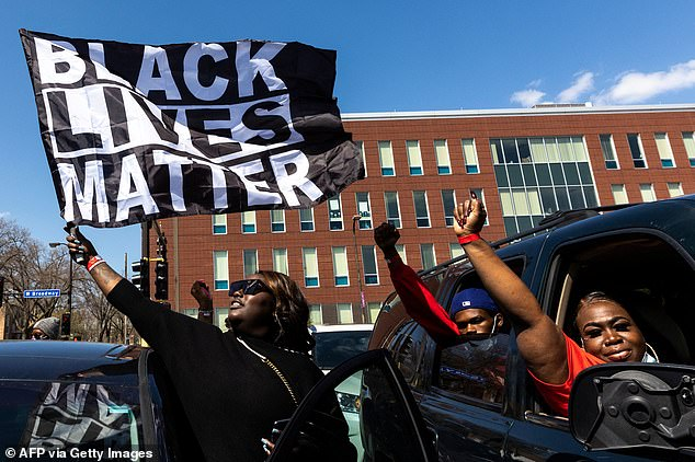 A woman holds a Black Lives Matter flag during the funeral service of Daunte Wright outside the Shiloh Temple on April 22