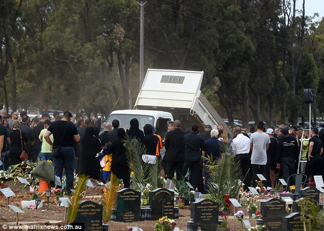 A tip truck pours soil over the body of slain former Comanchero leader Mick Hawi on Thursday