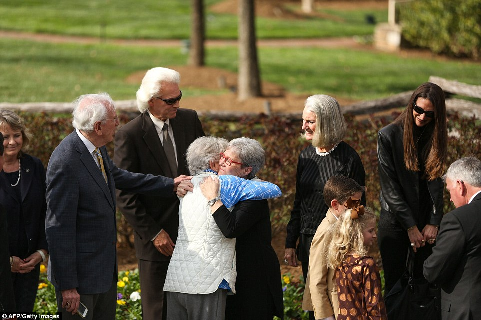 Family members are seen embracing one another. His grieving daughter Anne Graham Lotz is pictured second from the right