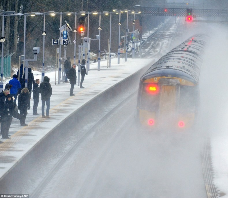 A train pulls into a snowy Petts Wood train station in South East London this morning as commuters try to get to work