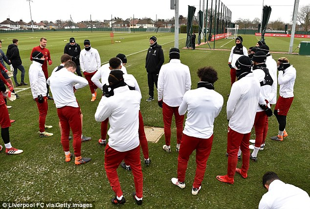 Klopp speaks with his squad as spots of snow are seen on the ground during a training session