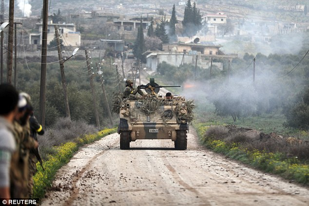 A Turkish-backed Free Syrian Army fighter fires from a tank in Rajo, Syria. Turkey said the town in the Afrin area had been cleared of 'terrorists'