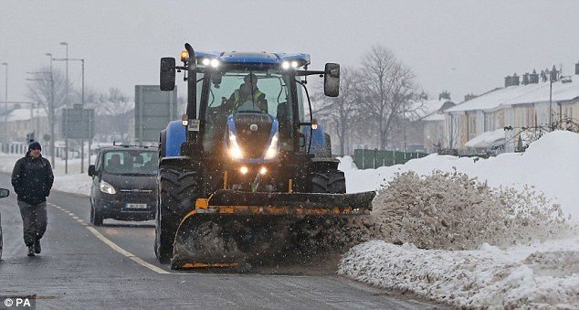 A snow plough is pictured desperately trying to clear grey sludge from the side of a road in Dublin, Ireland today
