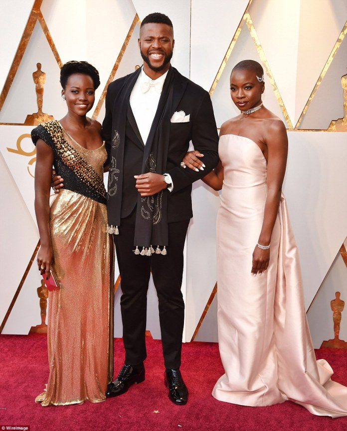 Talented group:The Black Panther beauty's ruched round-neck frock grazed the floor; she carried an on-trend clutch, adding diamond earrings and strappy black heels; pictured with her Black Panther co-stars Winston Duke and Danai Gurira