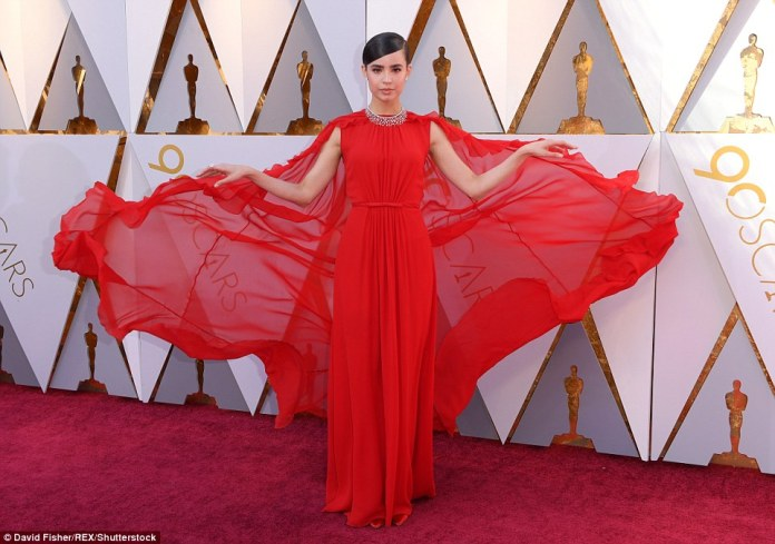 Lady in red: Sofia Carson stood out in this scarlet number with a wide, sheer cape that made her look ready to take flight; the dress is a Pre-Fall 2018 piece from Giambattista Valli