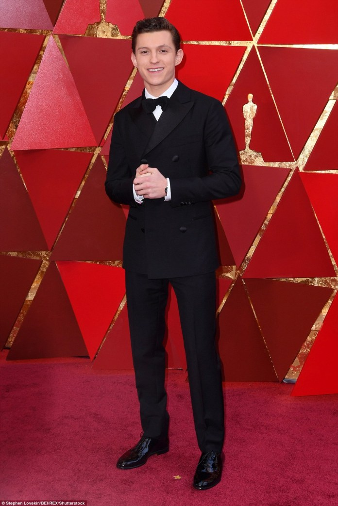 Smiling star: Tom Holland looked handsome in his black and white suit, complete with a bow tie; he wore custom Hermes