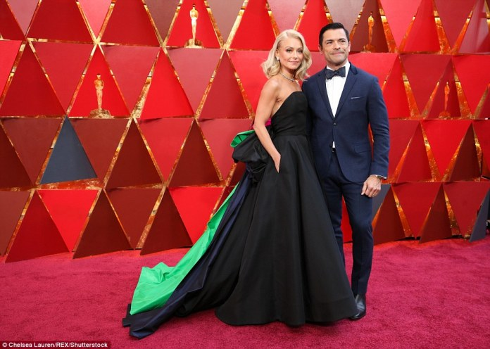 Bold accent: Kelly Ripa chose a black strapless gown with navy and green accents from Christian Siriano's Spring 2018 collection; pictured with husband Mark Consuelos