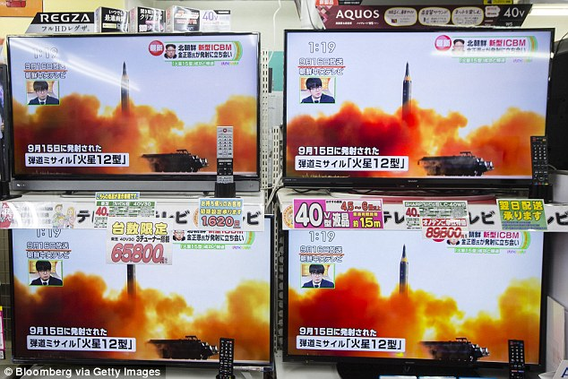 Televisions being sold at an Onoden Co. electronics store display a broadcast of a news report on North Korea's Nov. 29 missile launch, showing footage captioned as the launch of the Hwasong-12 missile in September, in Tokyo, Japan