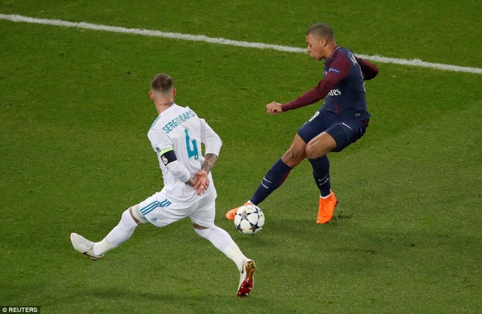 Madrid captain Ramos tries to halt the progress of France and PSG forward Kylian Mbappe during the first half in Paris