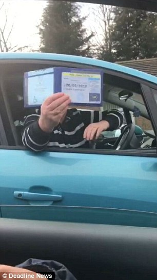The man held up his blue badge