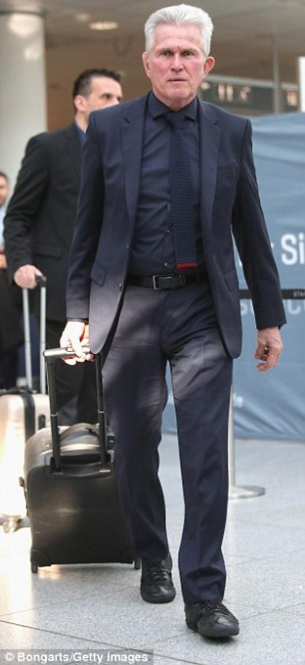 Head coach Jupp Heynckes wheels his case through the airport on Tuesday morning
