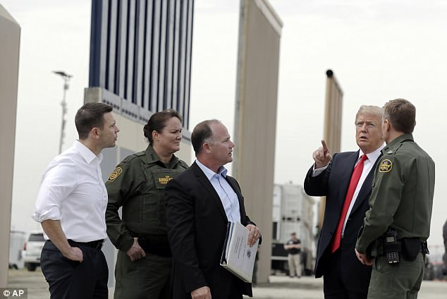 A number of border wall prototypes are seen looming behind President Trump (right) as he visits the state of California for the first time while in office