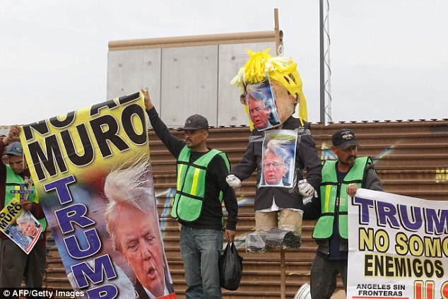 A pinata made to resemble the president is held up by a protester in Mexico Tuesday, as they stand along the current U.S.-Mexico border wall