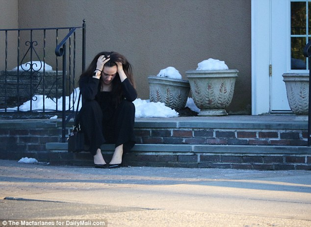 A woman is seen emotional sitting on the steps outside theDonohue Cecere Funeral Home