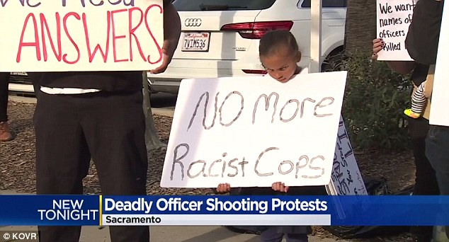 A boy is seen at Monday's protest holding up a large sign demanding 'No more racist cops'