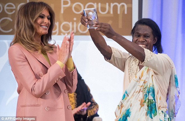 The first lady clapped while Godelieve Mukasarsi of Rwanda raised her award in the air
