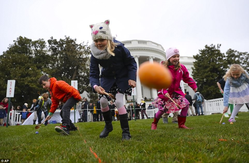 Participants at the 2018 White House Easter Egg Roll roll their eggs across the South Lawn on Monday