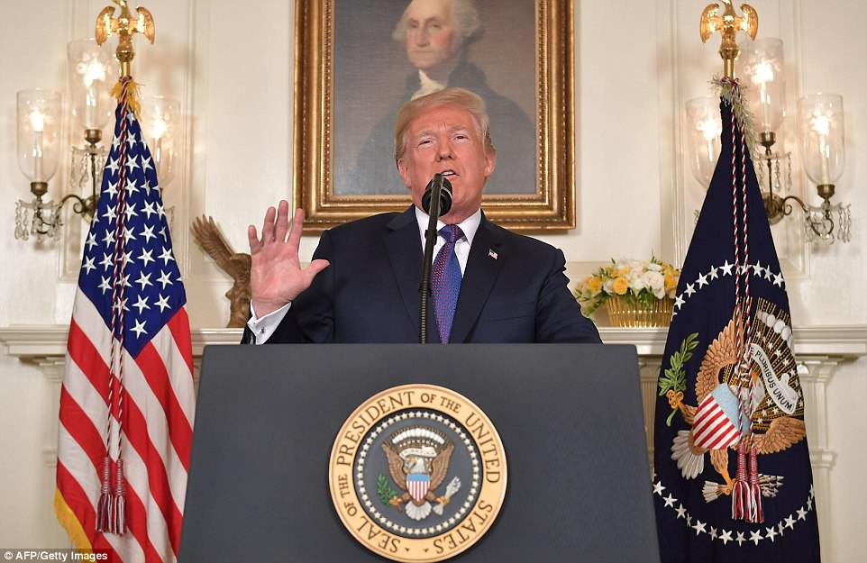 Donald Trump is pictured addressing the nation on Friday evening from the Diplomatic Room of the White House, announcing retaliatory airstrikes on Syria
