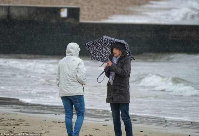 Two forecasters chat on the beach in Lyme Regis this morning after wet weather rained down on the seaside town