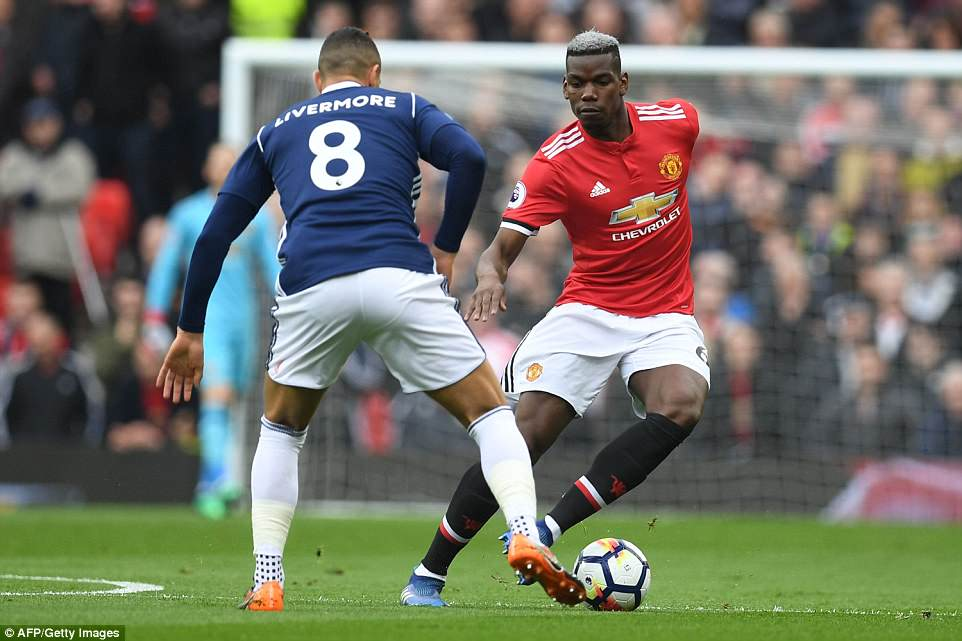 Manchester United midfielder Paul Pogba attempts to evade the challenge from West Brom counterpart Jake Livermore