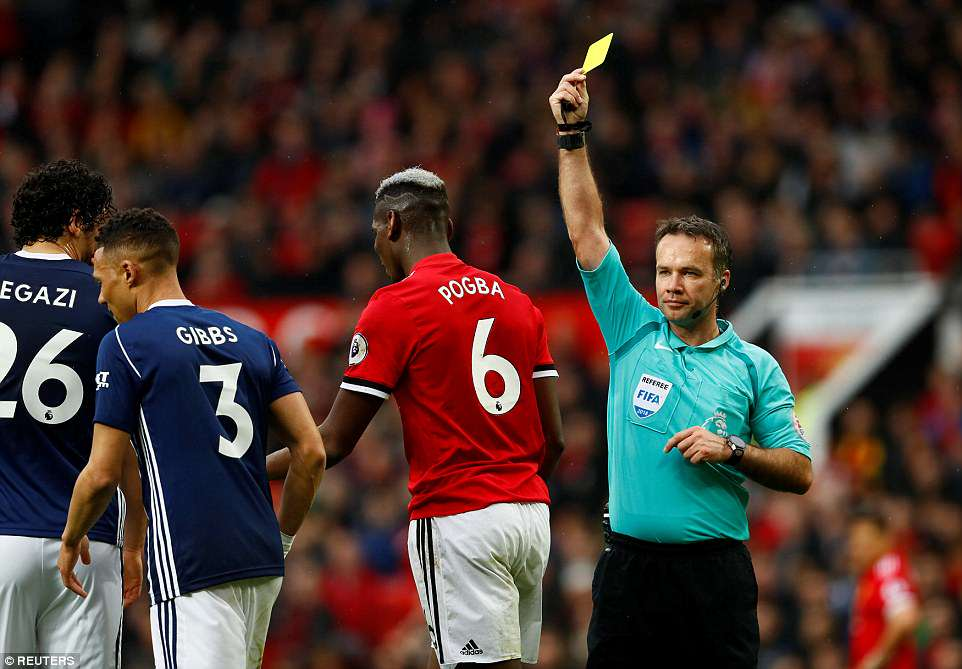 Manchester United midfielder Pogba is shown a yellow car by refereePaul Tierney for intentionally handling the football